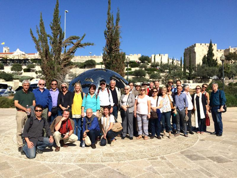 IF members gather in front of modern globe outside old walls of Jerusalem